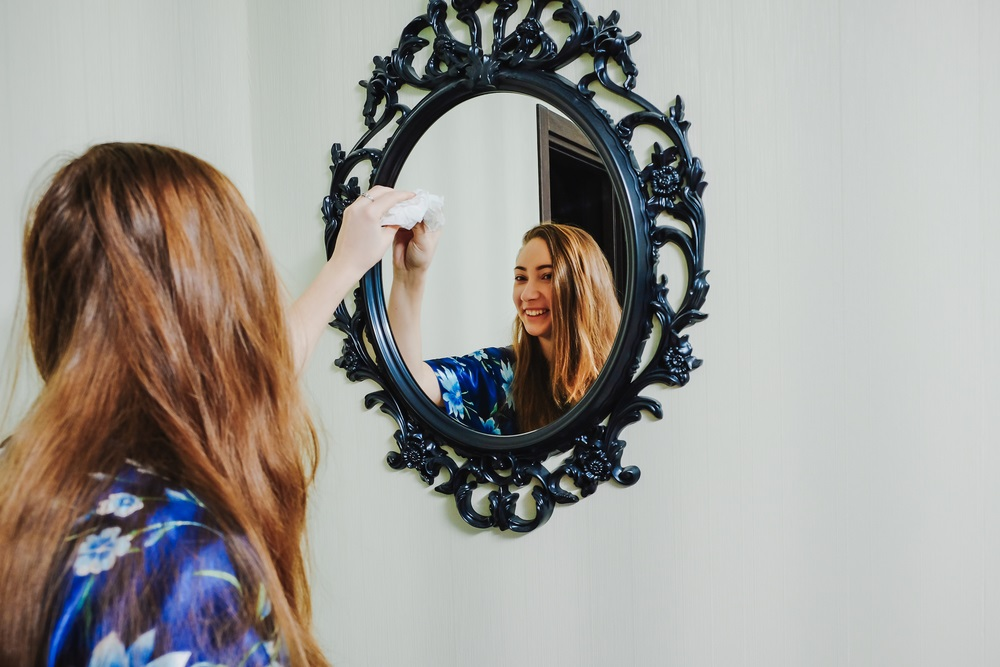 professional housecleaner cleaning a mirror